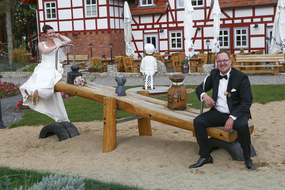 Glückliches Brautpaar gemeinsam auf Wippe vor Hochzeitslocation.