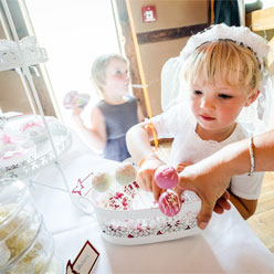 Kleine Hochzeitsprinzessin mit Süßigkeit vom Hochzeitsbuffet.