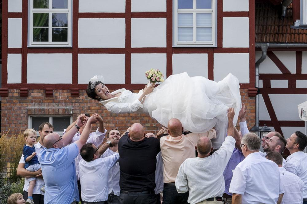 Männliche Hochzeitsgäste werfen braut freudig in die Luft.